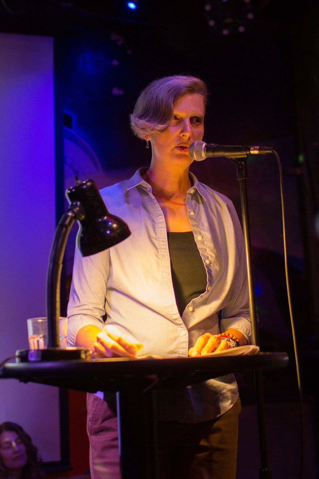 woman with short blonde hair standing at a microphone in a room with a darkened background